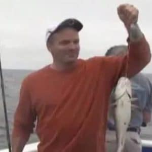 veteran holding a fish he caught by the line