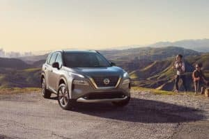 A 2021 Nissan Rogue parked on a mountain top with a city skyline in the valley