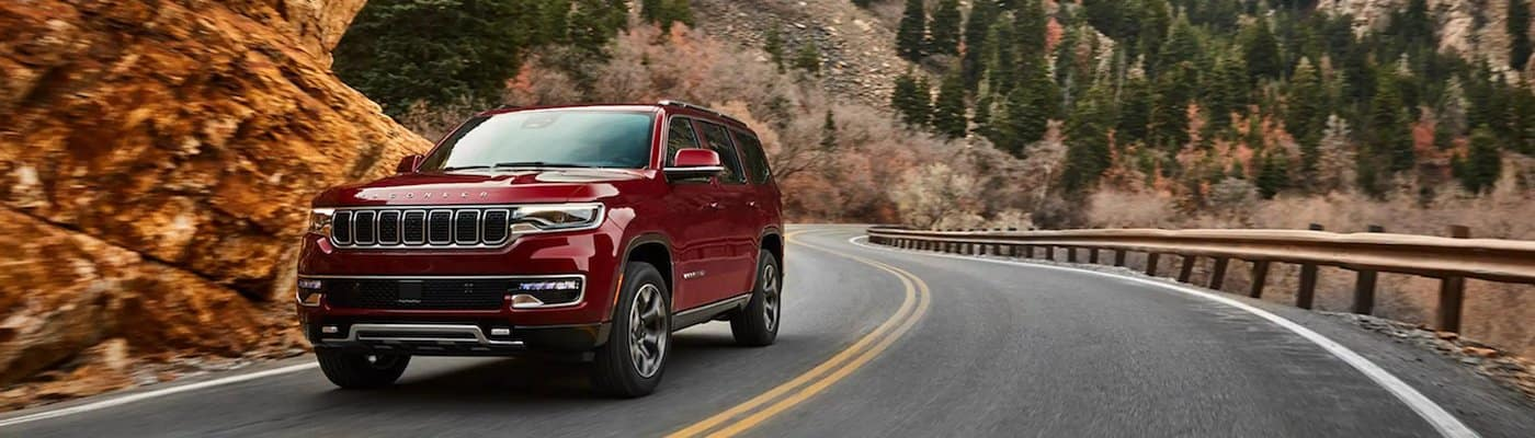Red 2022 Jeep Wagoneer driving down a mountain road