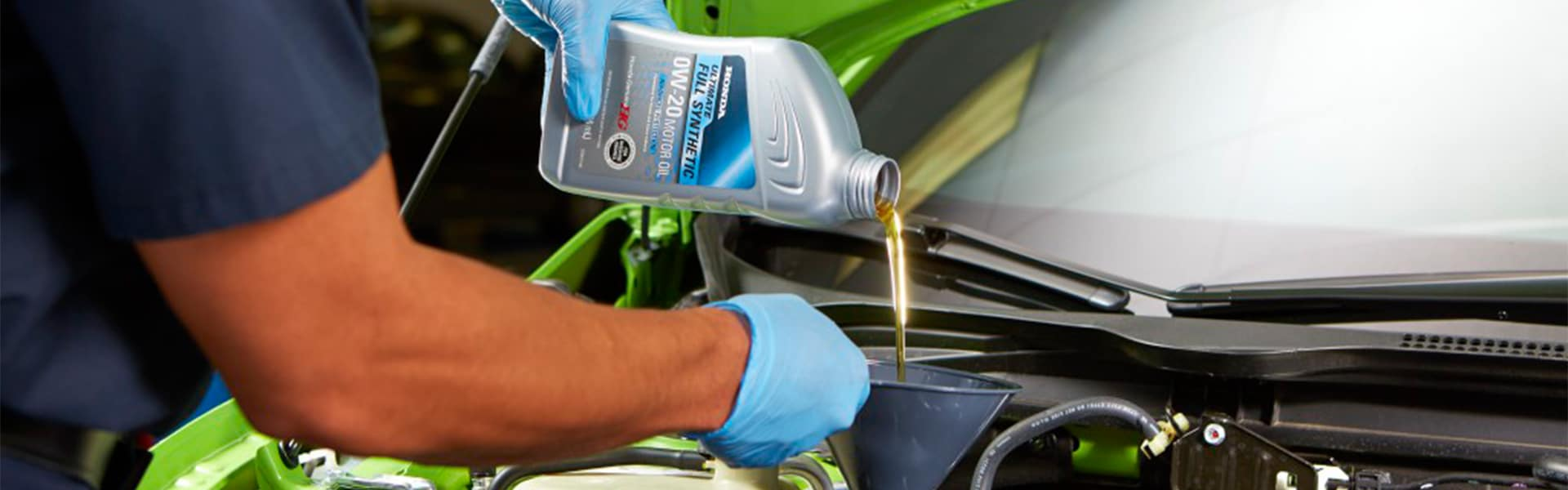 Benefits of Changing Your Honda's Oil at Washington Honda in Washington | Honda Service Advisor Pouring Genuine Honda Oil into Engine