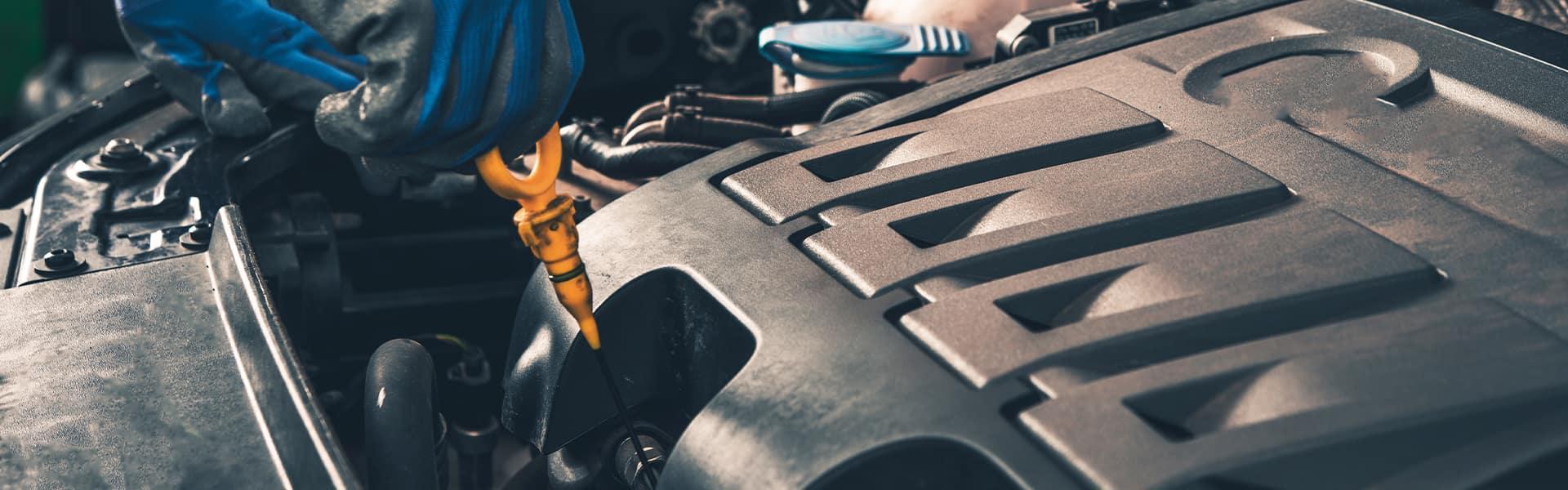 Benefits of Changing Your Honda's Oil at Washington Honda in Washington | Service Advisor Grabbing Oil Dip Stick From Engine