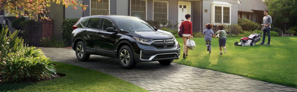 Washington Honda is a Honda Dealership in Washington near Peters Township PA   A family returning from grocery shopping by a 2021 Honda CR-V while the father mows the lawn