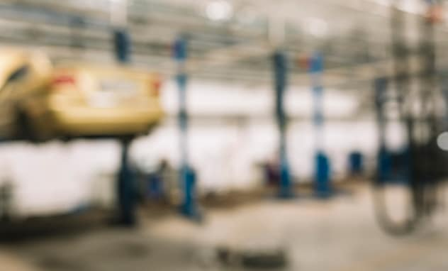 Washington Honda is a Honda Dealership in Washington near Peters Township PA   A blurry shot of a gold car on an auto lift