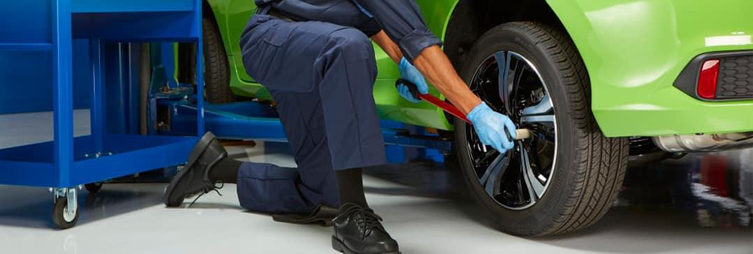 How to check your tires' health at Washington Honda of Washington | Mechanic on knee checking tire