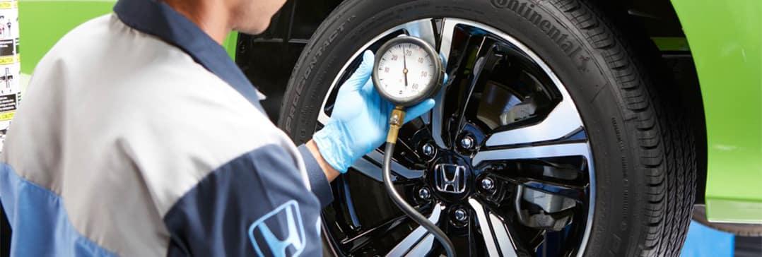 How to check your tires' health at Washington Honda of Washington | Mechanic inspecting tire pressure